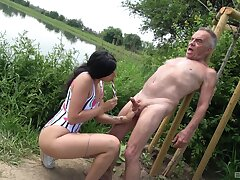 Jam-packed slut in a swimsuit gives an age-old impoverish a handy by the pond