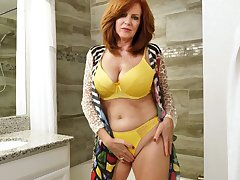 Red haired mature woman Andi James is taking a shower and masturbating pussy